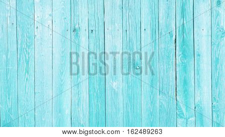 Natural Rustic Old Wood Board Wall Shabby Turquoise Color Background. Wooden Vintage Style Texture. Wood Surface Fence Panel with Peeling Paint Close up. Horizontal Wide Screen Image Copy Space