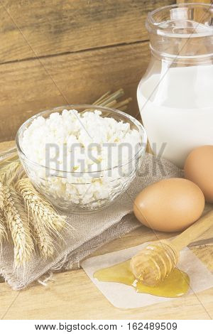 Organic Products: Eggs, Milk, Cottage Cheese, Honey, Butter, Wheat On A Wooden Background. Toning.