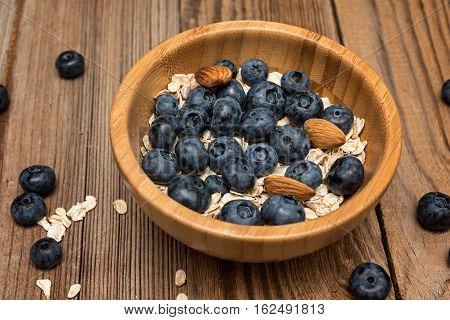 Healthy breakfast oatmeal honey and fresh berries on rustic background. Fresh granola and musli.