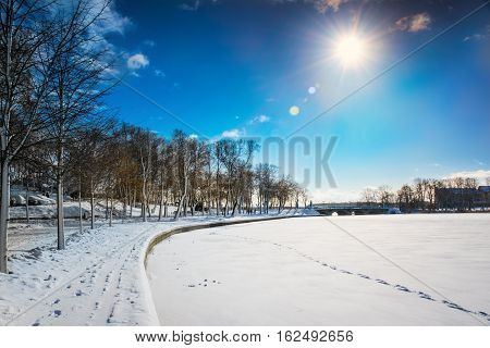 The Sun illuminates Elk promenade covered with snow. Masuria Poland.