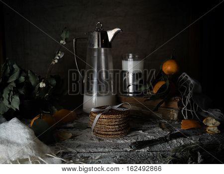 vintage. tangerines, tangerine slices, old milk jug, glass of on a wooden table.