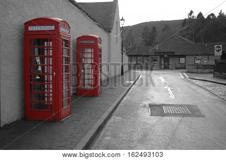 Two red phone boxes on black and white street.