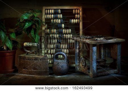 Vintage still life. On the table are antiques. Old wooden abacus accounting. Metal household items - iron, weight, primus. Nearby is a large vase in green plants. The photo was taken using a light brush effect it.