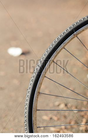 Close up shot of old bicycle wheel rim with tire on light brown background