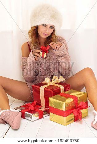 Beautiful woman unpacking christmas gifts, looking at camera.