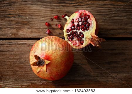 Two ripe pomegranate on a wooden table. One of pomegranates cut in half. From it fell a few red juicy seeds. The picture is removed from the top. Autumn harvest. Pomegranates are large and ripe. Peel pinkish berries with red spots. Aged wooden surface wit