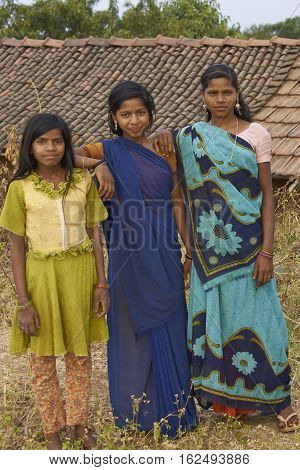 MANDU, INDIA - NOVEMBER 17, 2008: Trio of young Indian women wearing colourful sari's on a farm inside the hilltop fort of Mandu in Madyha Pradesh, India.