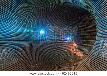Welder welding metal pipes in tunnel made of rounded steel pipes.