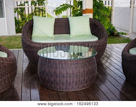 Patio Furniture set with green pillow int the garden