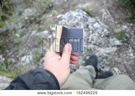 Male hand hold a book with text Discover