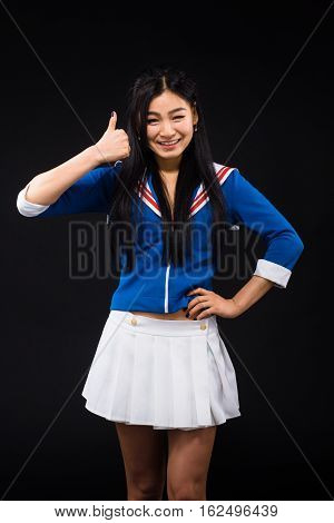 Asian woman showing thumb up or okay sign isolated on black. Brunette woman posing with her hand on hip, smiling for camera while expressing positive emotions in studio.