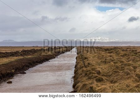 Endless straight canal sweeping through vast wide open grassland in Iceland to distant mountain range with snow ice and glacier on horizon.