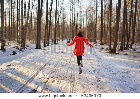 Young slender girl in a red coat runs along a snowy path in the Park fun bouncing and waving his arms.