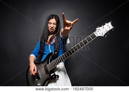 Asian rock star lady showing yo sign while playing guitar isolated on grey background in studio. Rock music concept.