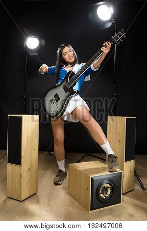 Beautiful Asian rock star lady playing hard rock while posing with guitar for photographer isolated on black background in studio.