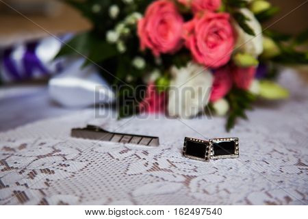 cuff links tie clasp to lie on a white background bouquet of pink and white roses groom's fees the preparation for the wedding style