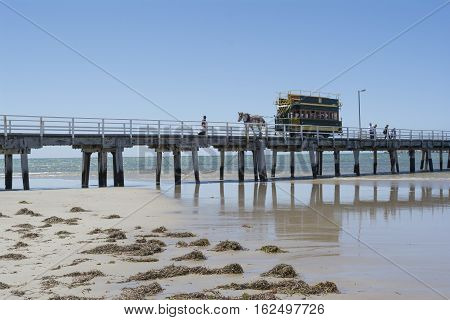 Victor Harbor SA Australia - Dec 20 2016: Horse Drawn Tram filled with tourists traveling along the bridge from Granite Island all reflected in the shallow water leeding up to the shore.