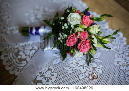infinity sign of the rings wedding rings on a white backgroundwedding bands bouquet of pink and white roses groom's fees the preparation for the wedding style wedding jewelry wedding preparation