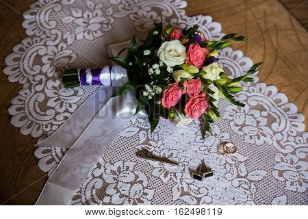 cuff links tie clasp to lie on a white background bouquet of pink and white roses groom's fees the preparation for the wedding style infinity sign of the rings wedding rings on a white backgroundwedding bands