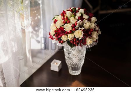 wedding flowers bouquet of white roses dairy and red flowers preparing for the wedding the groom's fees bride morning