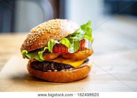 Hamburger With Cheese, Steak, Onion Rings And Salad.