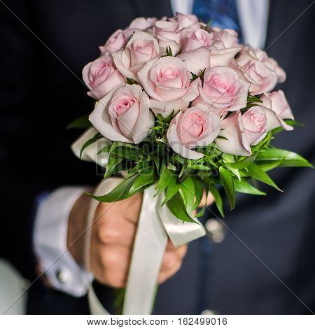 wedding flowers groom holds bouquet of pink roses bouquet of roses bridal bouquet groom's fees