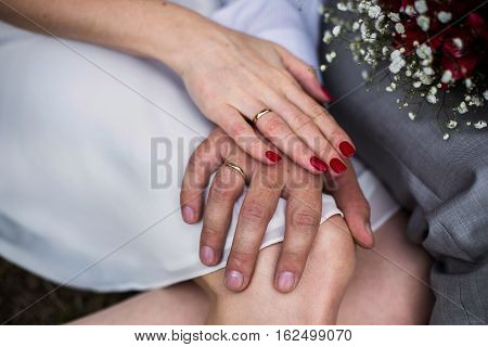 male and female hand with a wedding ring a female hand with red nails manicure love bouquet of red and white flowers wedding flowers wedding rings on hands