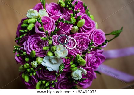 wedding flowersinfinity sign of the rings wedding rings on a white backgroundwedding bands wedding rings lie on a wedding bouquet of beautiful pink roses and white flowersbouquet of roses wedding preparation