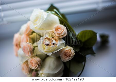 infinity sign of the rings wedding rings on a white backgroundwedding bands wedding rings lie on a bouquet of white and pink peach roses a bouquet of roses wedding flowers wedding bouquet