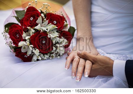 Bride and groom with wedding rings on their hands male and female hand with wedding rings wedding ceremony together forever wedding flowers wedding bouquet red roses