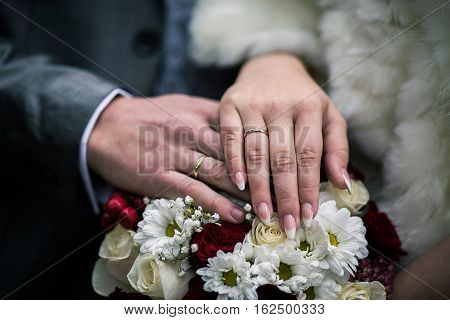 Bride and groom next to wedding rings on their hands male and female hand with wedding rings wedding ceremony together forever wedding flowers wedding bouquet hands on bouquet