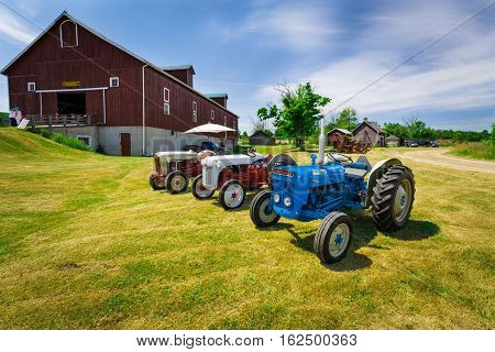 Milton, Ontario, Canada, June 18, 2016, amazing gorgeous  front side view of classic vintage retro tractors standing near the farm building in the park field on sunny summer beautiful day