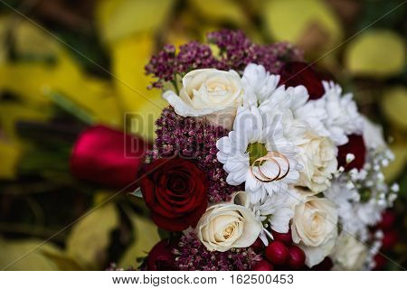 wedding flowers wedding rings lie on a wedding bouquet bouquet of red and peach dairy roses and white flowers lying on yellow autumn leaves wedding ceremony come autumn time of year the grass
