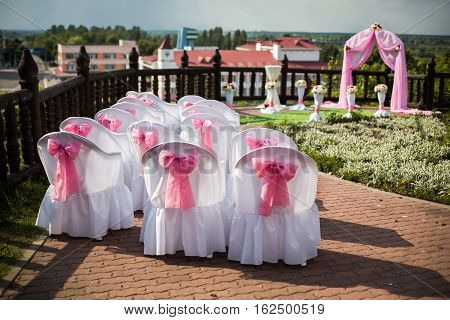 visiting wedding registration white chairs decorated for wedding pink wedding arch wedding flowers potted flowers white pink and red flowers wedding ceremony