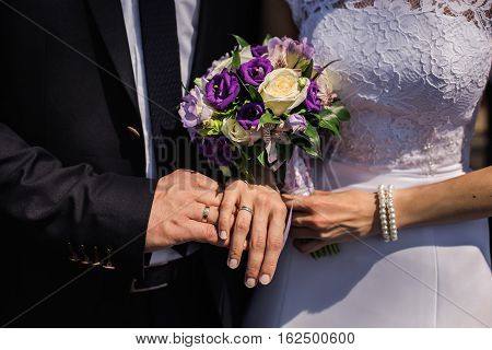 Bride and groom with rings on their hands male and female hand with wedding rings wedding ceremony together forever wedding flowers wedding bouquet hands on bouquet