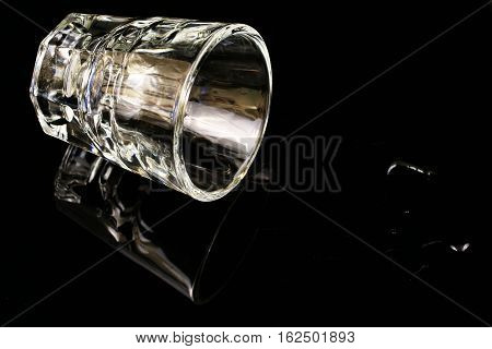 A shot glass tipped over on a black background