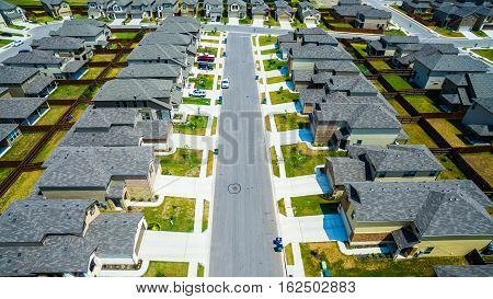 Bird's eye view over Modern Suburban Neighborhood in Austin Texas with rows of cookie cutter houses in a nice suburbia community