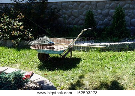 HARBOR SPRINGS, MICHIGAN / UNITED STATES - AUGUST 2, 2016: A rake lies in a wheelbarrow in the front yard of a home in Harbor Springs.