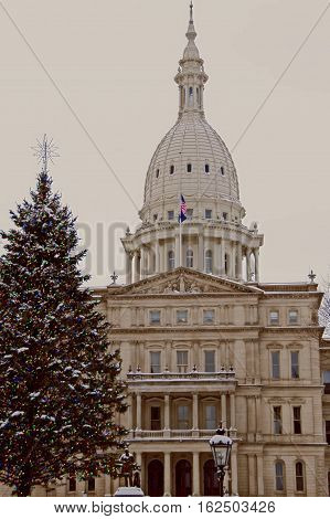 A photo of the State of Michigan Capitol Building with a Christmas tree in the foreground A photo of the State of Michigan Capitol Building with a Christmas tree in the foreground