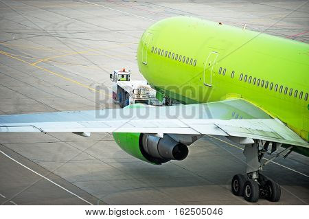 Towing big green airliner at an airport for departure