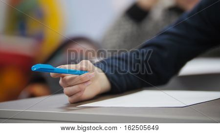 Child in classroom during the lesson - hand holding pen, close-up