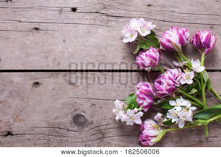 Tulips and apple tree flowers on aged wooden background. Selective focus. Place for text. Flat lay still life.