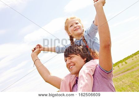 Little girl sitting on shoulders of her dad