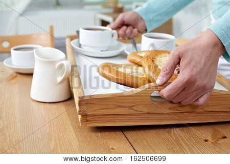 Close-up of female hands serving breakfast on the tray