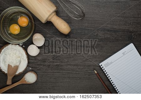 Baking ingredients (egg flour rolling pin) on a wooden table