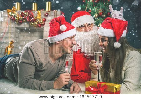 Young couple with Santa celebrating New Year 2017, Christmas party, drinking champagne. Twelve o'clock, midnight. Dressed in red hats.