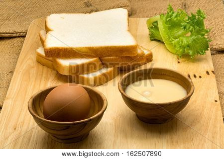 Pile of sliced breads sweetened condensed milk and egg on a wooden board