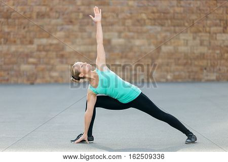 Sporty beautiful young woman practicing yoga, standing in Extended Side Angle exercise, Utthita parsvakonasana pose, working out, wearing sportswear, outdoor full length, brick wall background