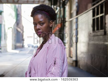 Portrait of young black woman in dark city street photographed in NYC in September
