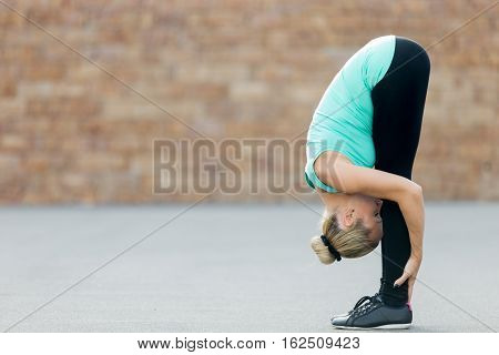 Sporty beautiful young woman practicing yoga, standing in forward bend, head to knees, exercise, uttanasana pose, working out, wearing sportswear, outdoor full length, brick wall background. Copy space